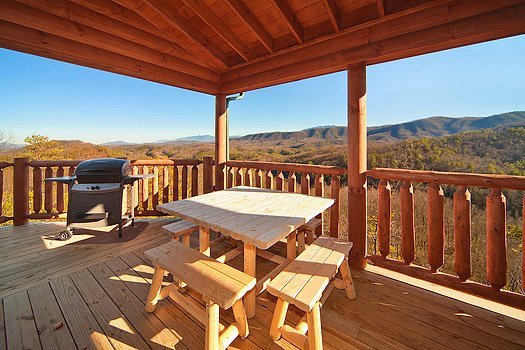 picnic table and grill on deck with smoky mountain views at horse'n around a 3 bedroom cabin rental located in pigeon forge