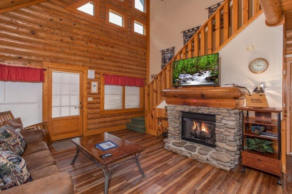 Living room with fireplace and TV at Starry Starry Night #725, a 2 bedroom cabin rental located in Pigeon Forge