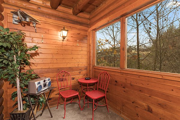 Screened porch with bistro set and CD player at Starry Starry Night #725, a 2 bedroom cabin rental located in Pigeon Forge
