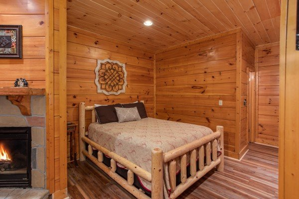 Bedroom with a log bed and fireplace at Starry Starry Night #725, a 2 bedroom cabin rental located in Pigeon Forge