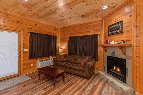 Sofa bed and fireplace on the first floor at Starry Starry Night #725, a 2 bedroom cabin rental located in Pigeon Forge