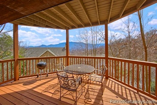main level deck with grill and patio table at Gatlinburg Getaway, a 3-bedroom cabin rental located in Gatlinburg