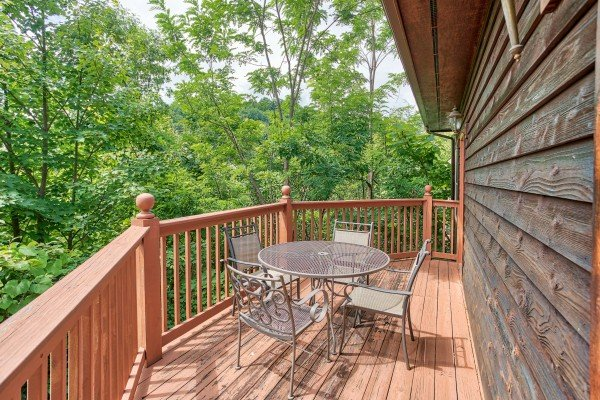 Outdoor dining space for four on the deck at Gatlinburg Getaway, a 3-bedroom cabin rental located in Gatlinburg