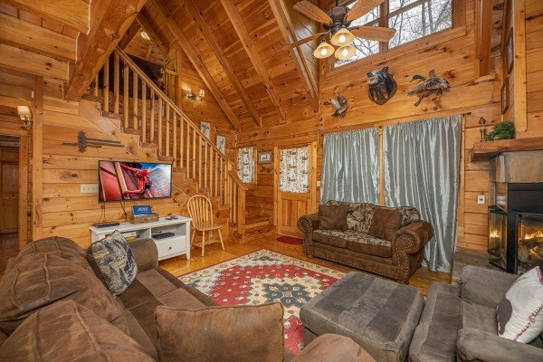 Two sofas, chaise, fireplace, and TV in the living room at Fox Ridge, a 3 bedroom cabin rental located in Pigeon Forge