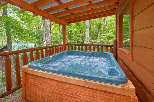 Hot tub on a covered deck at Pop's Snuggle Bear, a 1 bedroom cabin rental located in Pigeon Forge