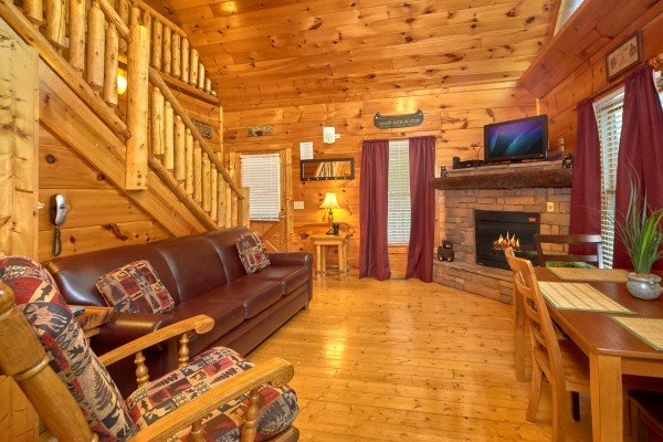 Living room with fireplace, TV, and dining space at Pop's Snuggle Bear, a 1 bedroom cabin rental located in Pigeon Forge
