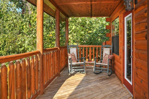 Covered deck with rocking chairs and wooded surround at Kick Back & Relax! A 4 bedroom cabin rental located in Pigeon Forge