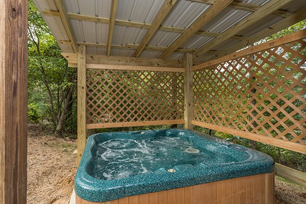 Hot tub on a covered patio with lattice fence at Bird's Eye View, a 2-bedroom cabin rental located in Gatlinburg