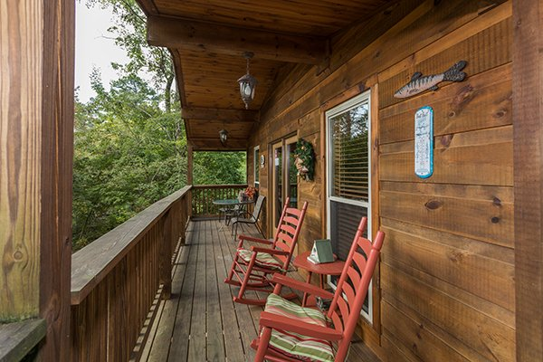 Rocking chairs on a covered deck at Bird's Eye View, a 2-bedroom cabin rental located in Gatlinburg