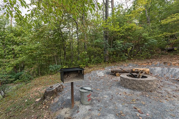 Firepit with log seating and charcoal grill at Bird's Eye View, a 2-bedroom cabin rental located in Gatlinburg
