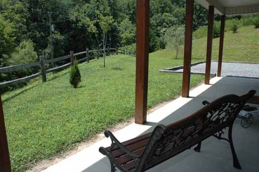 Bench by the front door looking out into the yard at Heaven Sent, a 2-bedroom cabin rental located in Pigeon Forge