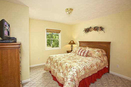 King sized bed with tv a chest of drawers at Heaven Sent, a 2-bedroom cabin rental located in Pigeon Forge