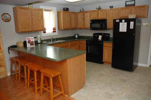 Kitchen with counter seating for four and black appliances at Heaven Sent, a 2-bedroom cabin rental located in Pigeon Forge