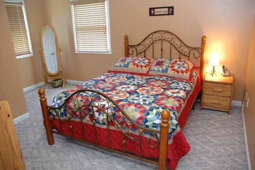 queen sized bed with dressing mirror at heaven sent a 2 bedroom cabin rental located in pigeon forge