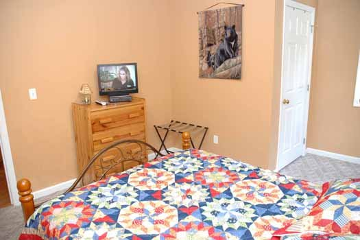 Bedroom with a TV and dresser at Heaven Sent, a 2-bedroom cabin rental located in Pigeon Forge