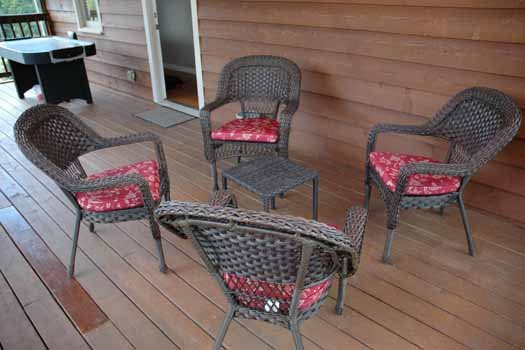 Wicker patio set on the screened deck at Heaven Sent, a 2-bedroom cabin rental located in Pigeon Forge