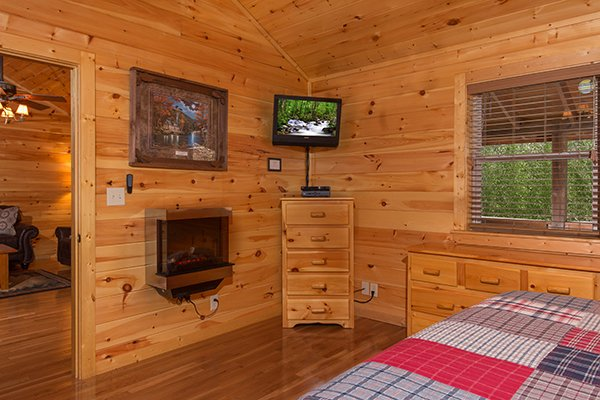 Bedroom with an electric fireplace and TV at Rustic Romance, a 2 bedroom cabin rental located in Pigeon Forge