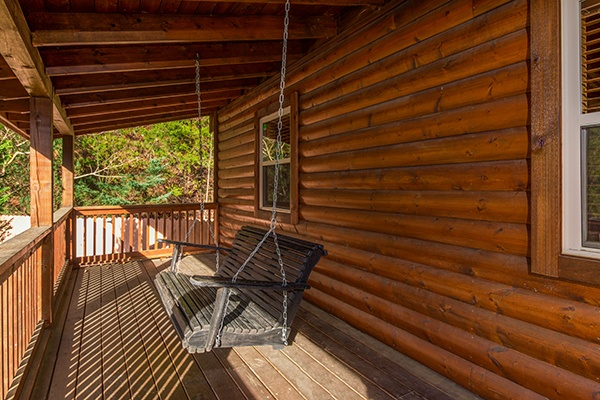 Swing on a covered porch at Rustic Romance, a 2 bedroom cabin rental located in Pigeon Forge