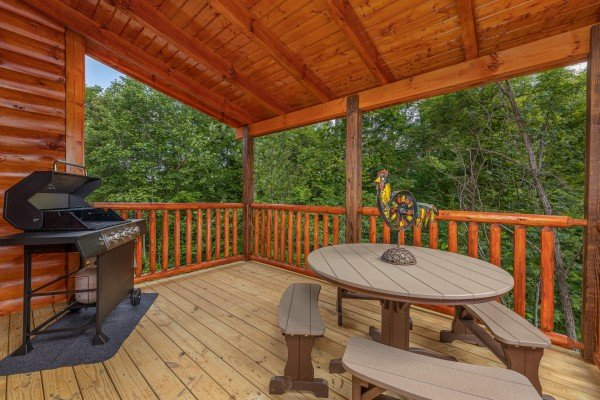 Grill and dining table on a covered deck at Mountain Life, a 2 bedroom cabin rental located in Pigeon Forge