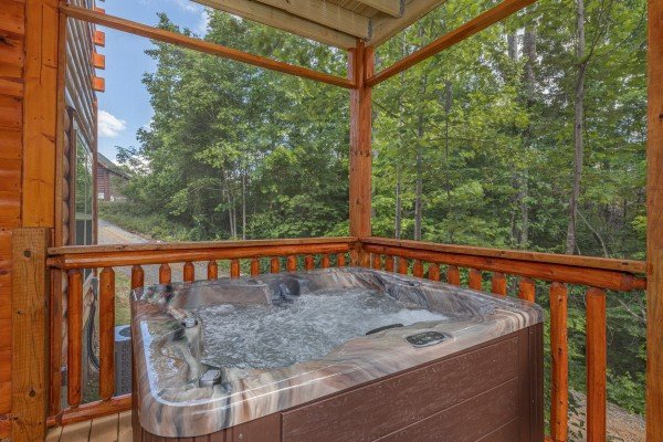 Hot tub on a covered deck at Mountain Life, a 2 bedroom cabin rental located in Pigeon Forge