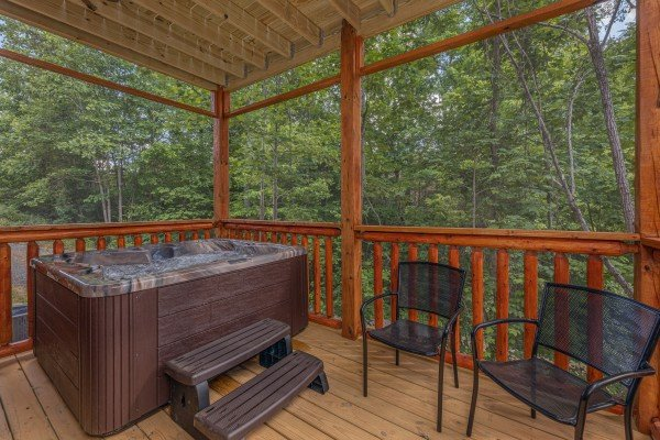 Hot tub and chairs on a covered deck at Mountain Life, a 2 bedroom cabin rental located in Pigeon Forge