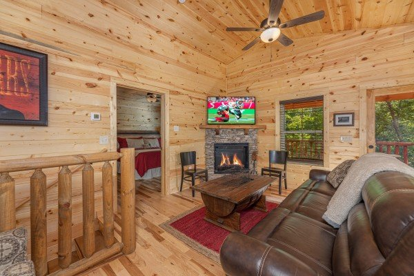 Living room with fireplace and TV at Mountain Life, a 2 bedroom cabin rental located in Pigeon Forge
