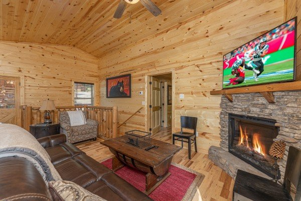 Seating, fireplace, and TV in a living room at Mountain Life, a 2 bedroom cabin rental located in Pigeon Forge