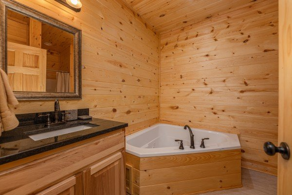 Bathroom with a corner jacuzzi at Mountain Life, a 2 bedroom cabin rental located in Pigeon Forge