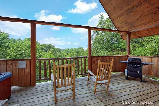 Back deck with grill and rockers at Swept Away, a 1 bedroom cabin rental located in Pigeon Forge