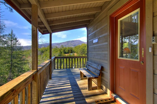 Bench by the front door on the deck at Cabin on the Hill, a 1-bedroom cabin rental located in Pigeon Forge