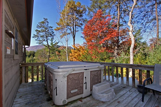 Hot tub with fall colors on the trees around Cabin on the Hill, a 1-bedroom cabin rental located in Pigeon Forge