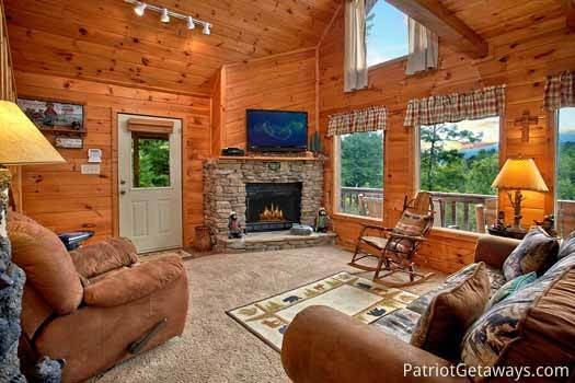 Living room with stone fireplace and sofa bed at Cabin on the Hill, a 1-bedroom cabin rental located in Pigeon Forge