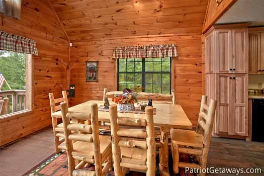 Dining table with four chairs and a bench at Cabin on the Hill, a 1-bedroom cabin rental located in Pigeon Forge