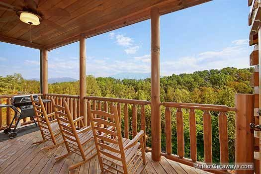 rockers on the deck with a grill at majestic mountain view a 2 bedroom cabin rental located in pigeon forge
