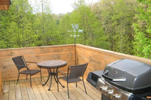gas grilll with table and chairs on the deck at lazy rooster a 2 bedroom cabin rental located in gatlinburg