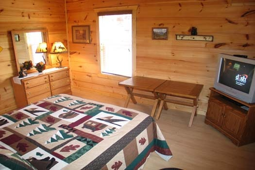 dresser and tv in bedroom at lazy rooster a 2 bedroom cabin rental located in gatlinburg