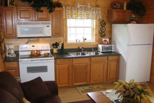kitchen with white appliances at lazy rooster a 2 bedroom cabin rental located in gatlinburg