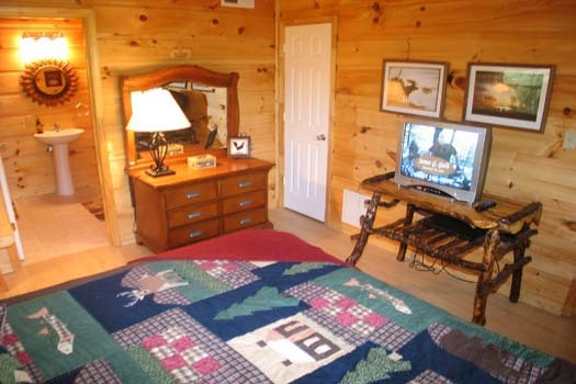 tv and dresser in bedroom at lazy rooster a 2 bedroom cabin rental located in gatlinburg
