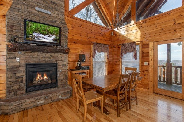 Fireplace with TV and dining set at 5 Star View, a 3 bedroom cabin rental located in Gatlinburg