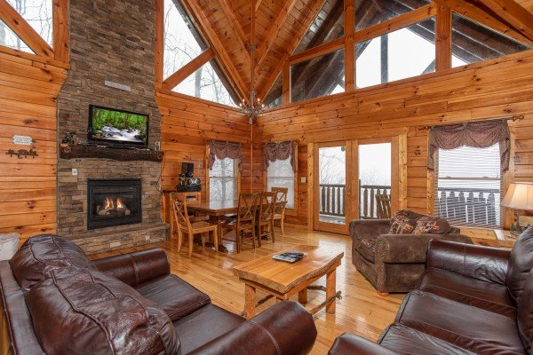Main floor living room, fireplace, TV, dining space, and deck access at 5 Star View, a 3 bedroom cabin rental located in Gatlinburg