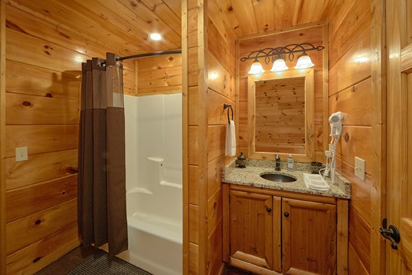 Bathroom with a tub and shower at Makin' Honey, a 1 bedroom cabin rental located in Pigeon Forge