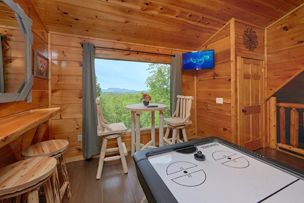Bar top table for two, air hockey table, and TV in the game loft at Makin' Honey, a 1 bedroom cabin rental located in Pigeon Forge
