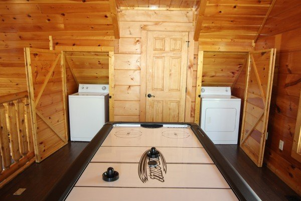 Air hockey table and laundry machines in the loft at Makin' Honey, a 1 bedroom cabin rental located in Pigeon Forge