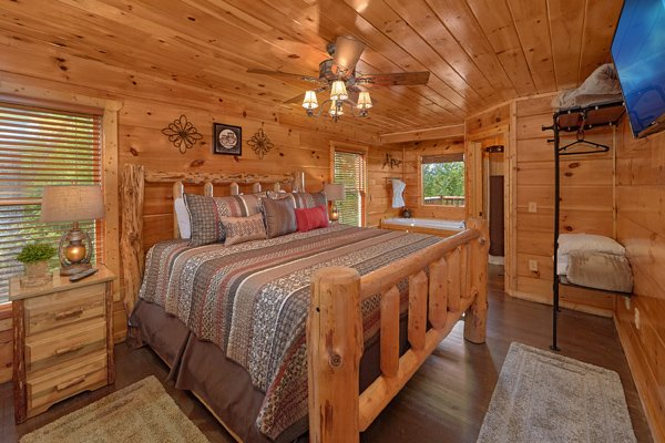 Bedroom with a king-sized log bed at Makin' Honey, a 1 bedroom cabin rental located in Pigeon Forge