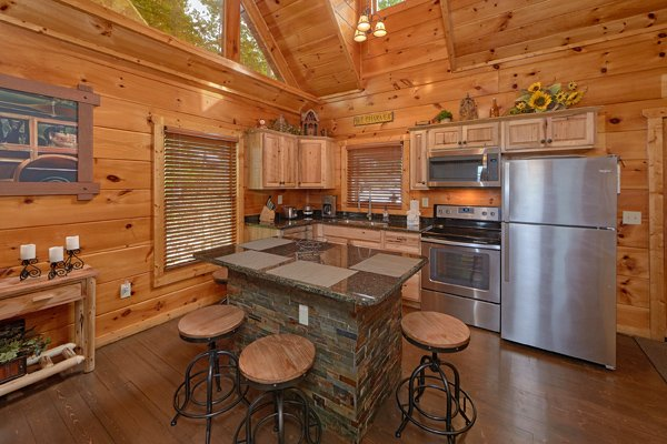 Kitchen with stainless appliances, granite counters, and bar seating for four at Makin' Honey, a 1 bedroom cabin rental located in Pigeon Forge