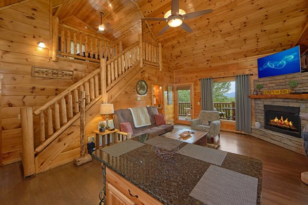 Living room with fireplace and TV at Makin' Honey, a 1 bedroom cabin rental located in Pigeon Forge