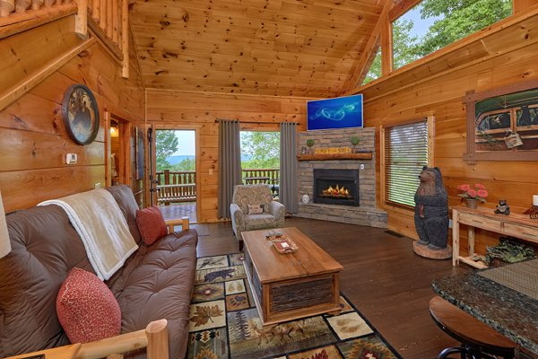 Living room with fireplace, TV, and deck access at Makin' Honey, a 1 bedroom cabin rental located in Pigeon Forge