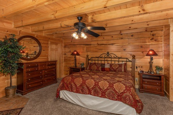 King bed, two night stands, and a dresser in the bedroom at Little Chateau, a 1 bedroom cabin rental located in Pigeon Forge