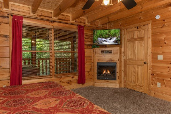 Fireplace & TV in the bedroom at Little Chateau, a 1 bedroom cabin rental located in Pigeon Forge