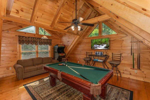 Pool table, sleeper sofa, and video game in the game loft at Little Chateau, a 1 bedroom cabin rental located in Pigeon Forge